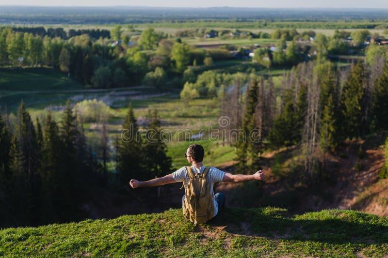 Touriste de jeune homme avec le sac à dos se tenant au bord du beau canyon et des mains victorieusement augmentées Randonneur mâl photos stock