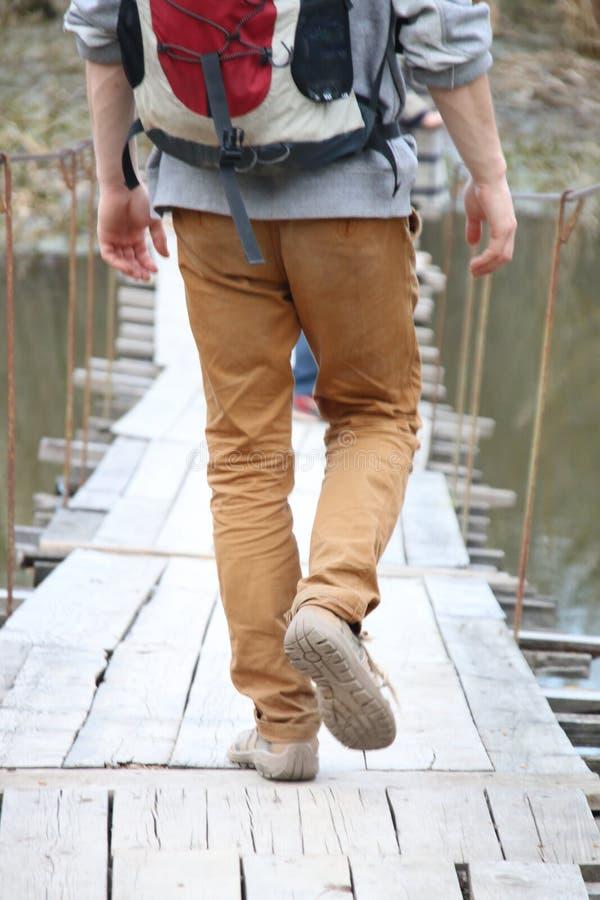 Touriste et voyageur marchant loin sur un pont suspendu en bois photo stock