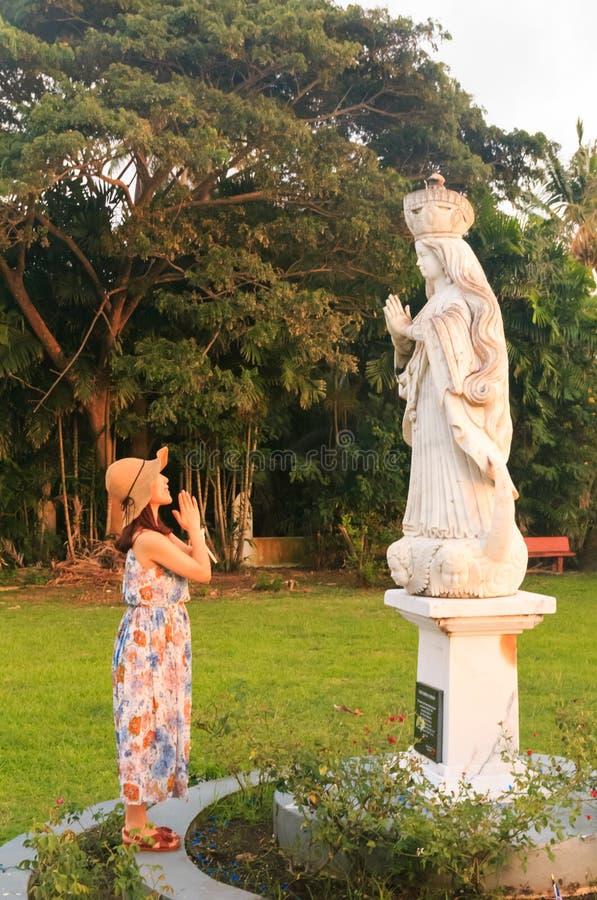 Touriste féminin asiatique priant avec la statue de Vierge Marie images libres de droits