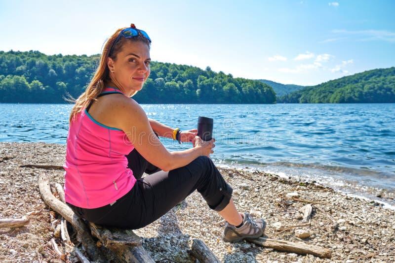 Touriste féminin détendu avec une tasse de café isolée thermique dans des mains, s'asseyant sur un rondin à un rivage de lac de m image stock