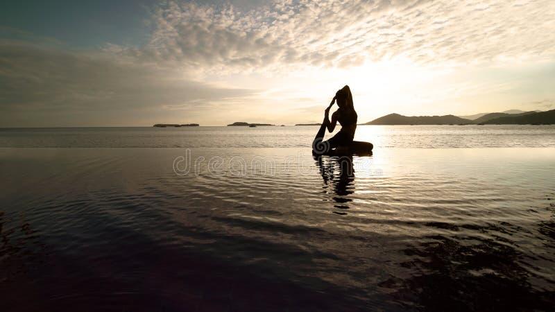 Touriste f?minin faisant le yoga dans la pose de pigeon de roi image libre de droits
