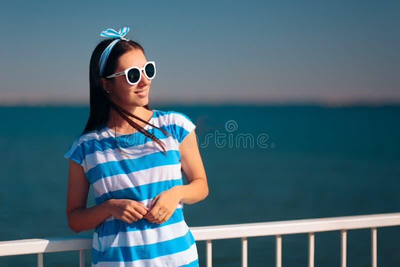 Touriste féminin gai avec le T-shirt et les lunettes de soleil dépouillés de marine images stock