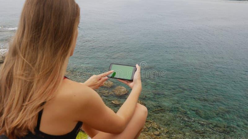 Touriste féminin s'asseyant sur une roche sur le fond de ciel clair et de mer calme images libres de droits