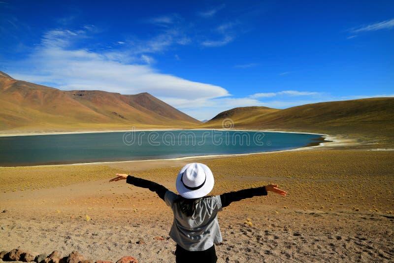 Touriste féminin soulevant ses bras admirant la lagune bleue profonde étonnante Laguna Miniques, Chili photo libre de droits