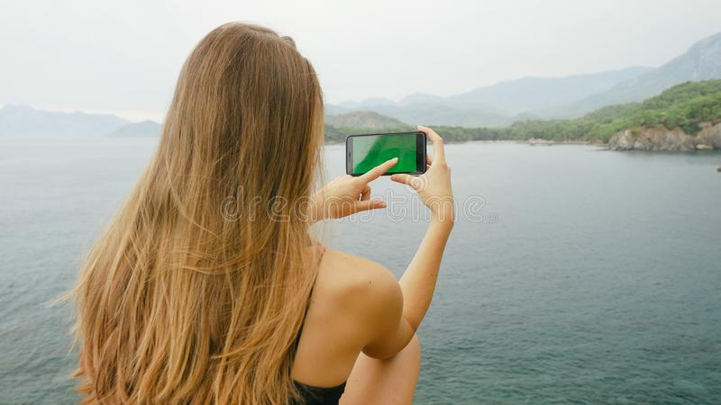 Touriste f?minin s'asseyant sur une roche sur le fond de ciel clair et de mer calme photo stock