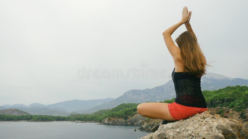 Touriste f?minin s'asseyant sur une roche sur le fond de ciel clair et de mer calme image stock