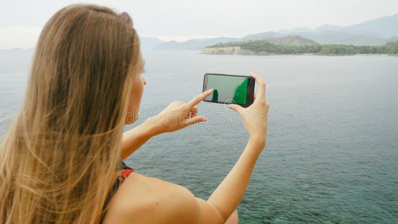 Touriste f?minin s'asseyant sur une roche sur le fond de ciel clair et de mer calme photo libre de droits