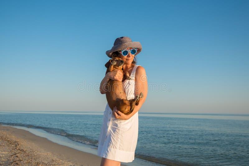 Touriste heureuse de femme, dans lunettes de soleil drôles, avec un petit chien photo stock