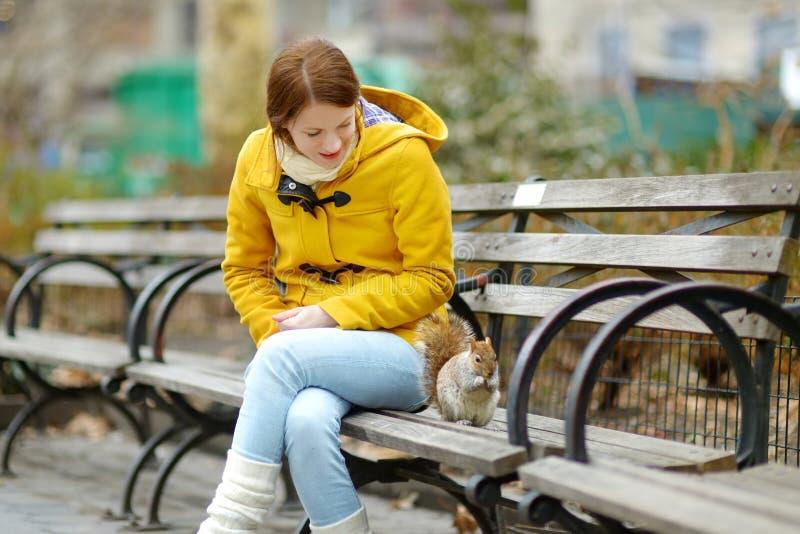 Touriste heureux de jeune femme alimentant un écureuil en Madison Square Park, New York City, à la journée de printemps ensoleill photographie stock libre de droits