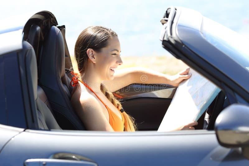 Touriste lisant une carte à l'intérieur d'une voiture des vacances images stock