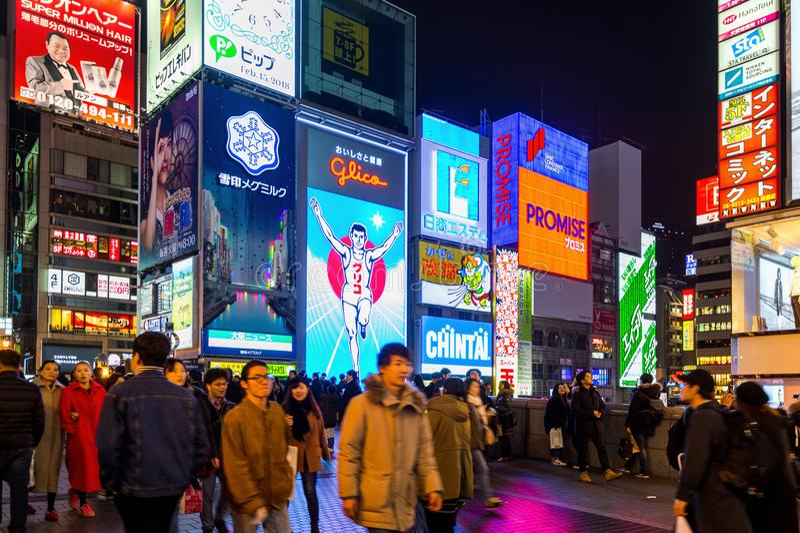 Touriste marchant dans la rue d'achats de nuit chez Dotonbori à Osaka, Japon photographie stock