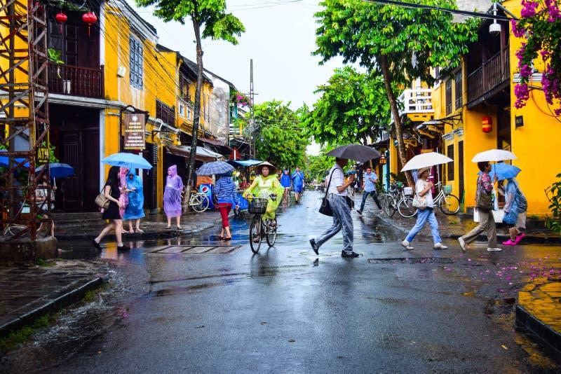 Touriste prenant une visite pour découvrir la promenade de ville antique de Hoi An un jour pluvieux photos libres de droits