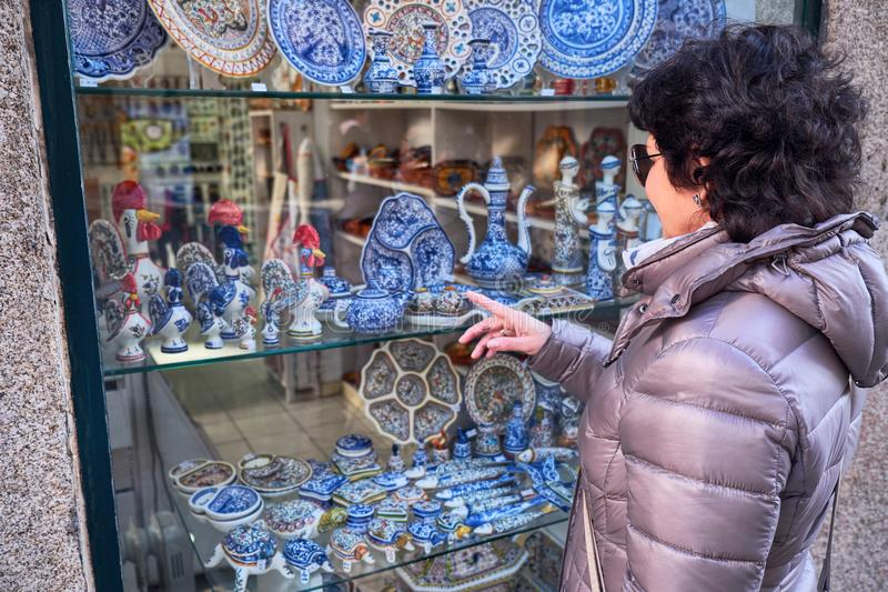 Touriste, regardant par une fenêtre dans la boutique avec les marchandises traditionnelles à Porto, le Portugal photos stock
