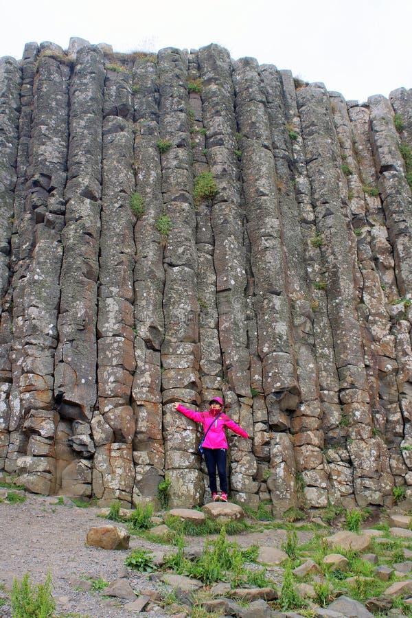 Touriste se tenant contre des colonnes de basalte images stock