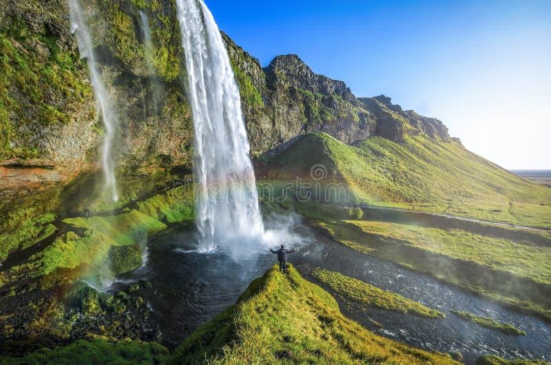 Touriste se tenant devant Seljalandsfoss avec l'arc-en-ciel autour, beau paysage étonnant d'Islande, photos stock