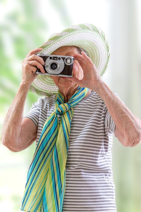 Touriste supérieure heureuse de femme avec le chapeau prenant des photos dans la nature photographie stock libre de droits