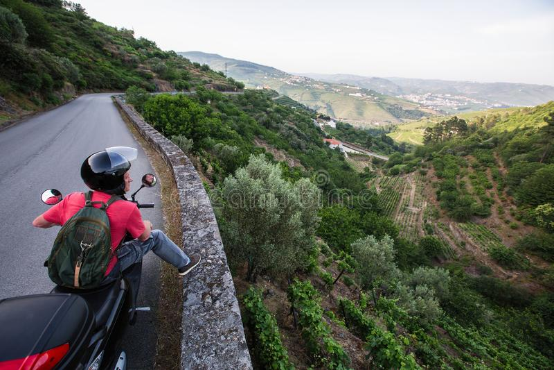 Touriste sur des tours d'une motocyclette sur une route serpentine au point de vue de la vallée de Douro, Porto photos stock
