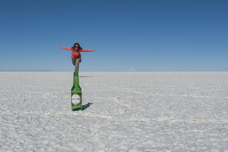 Touriste sur l'appartement de sel d'Uyuni jouant avec la perspective spatiale, créant une illusion visuelle images stock