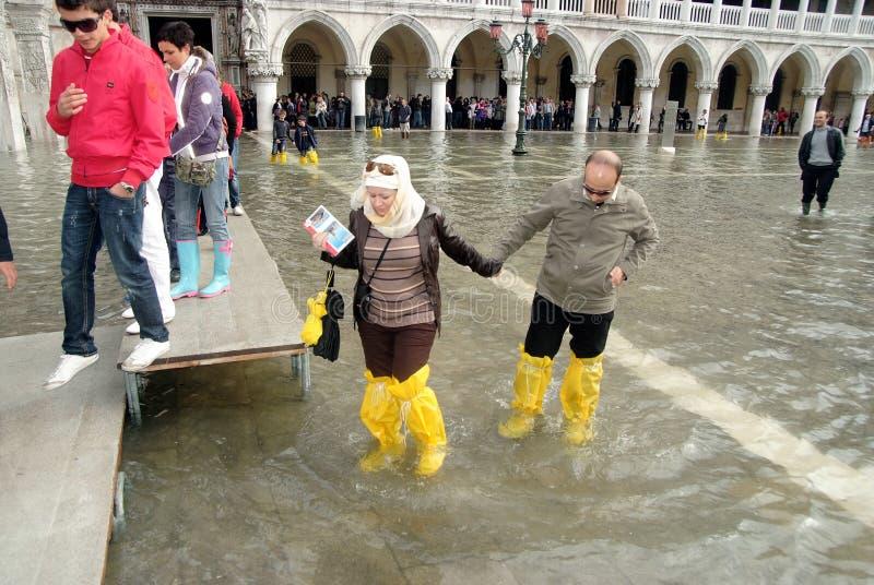 Touristen auf überschwemmtem Stadtplatz lizenzfreie stockfotografie