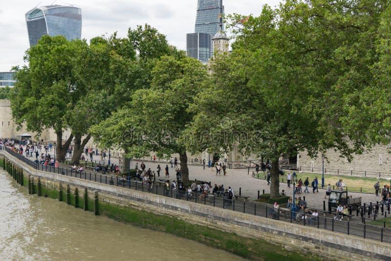 Touristen auf Banken von der Themse in London, England außerhalb des Tower von London stockbild