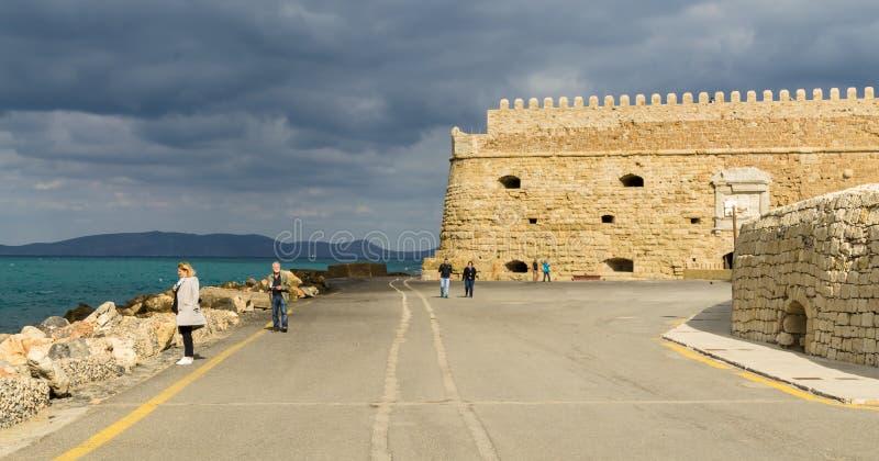 Touristen auf dem Damm nahe der Bastion der alten venetianischen Festung Koule, Iraklio-Hafen, Kreta lizenzfreies stockfoto