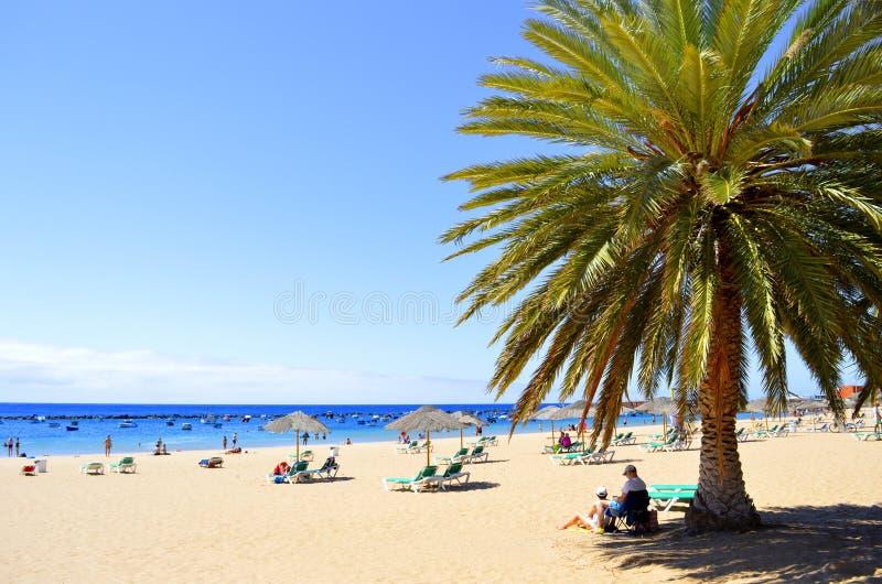 Touristen auf dem Strand die Sonne genießend lizenzfreie stockfotografie