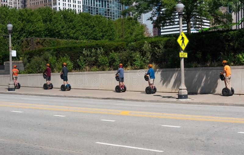 Touristen auf, die den seagways reiten durch eine Straße von Chicago sind stockfotos