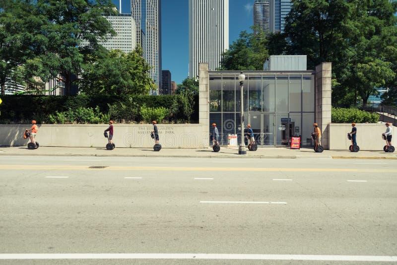 Touristen auf, die den seagways reiten durch eine Straße von Chicago sind stockfotografie