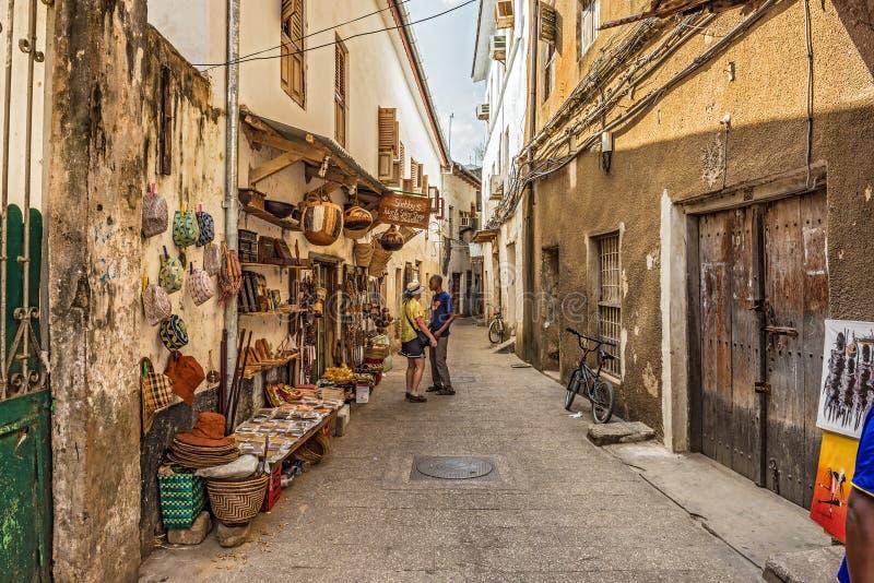 Touristen auf einer typischen schmalen Straße in der Steinstadt, Sansibar lizenzfreie stockfotos