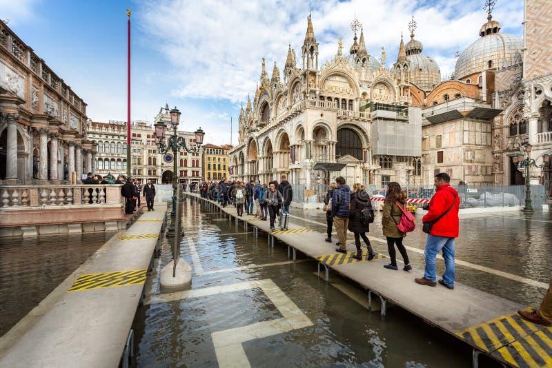 Touristen auf Entenbrettern in überschwemmten St Mark Quadrat in Venedig, Italien stockbild