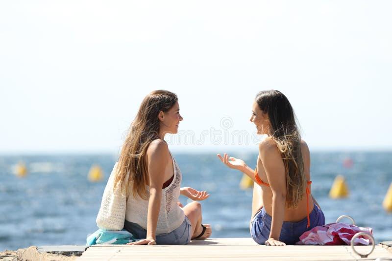 Touristen auf Sommer vacartions sprechend auf dem Strand lizenzfreie stockfotos