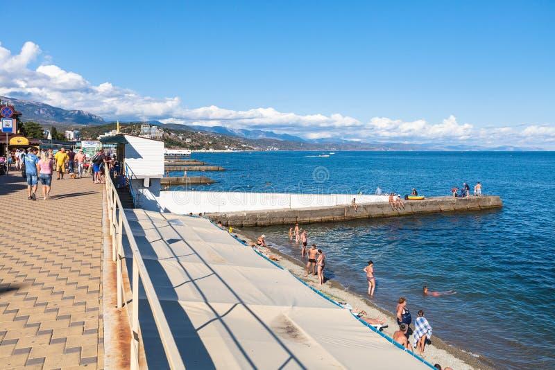 Touristen auf Strand entlang Damm in Alushta lizenzfreies stockfoto