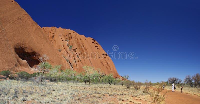 Touristen auf Uluru Unterseiten-Weg lizenzfreies stockfoto
