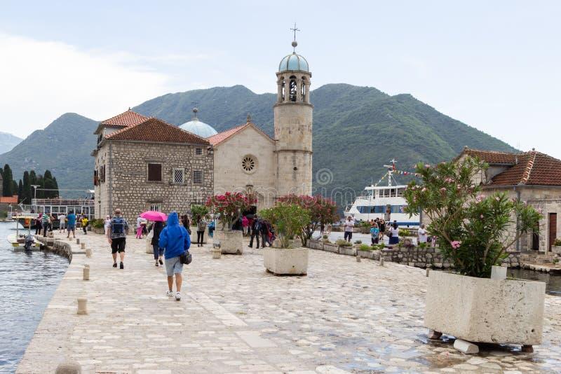 Touristen beaufsichtigen die Insel von Gospa Od Skrpjela unsere Dame der Felsen in der Bucht von Kotor stockbilder