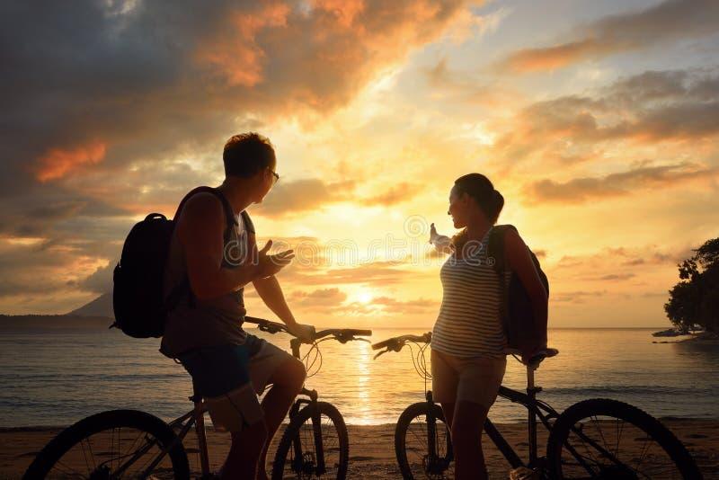 Touristen des glücklichen Paars mit Fahrrädern Sonnenuntergang aufpassend Schattenbild stockfotos