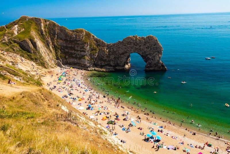 Touristen, die auf Durdle-Tür-Strand, Dorset sich entspannen stockbild