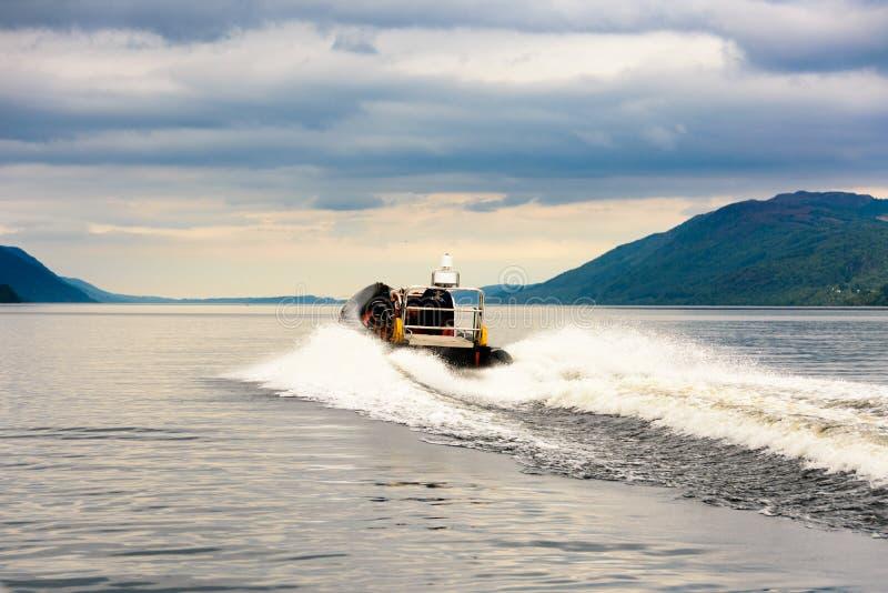 Touristen, die auf einem RIPPEN-Boot, Loch Ness speedboating sind stockfotografie