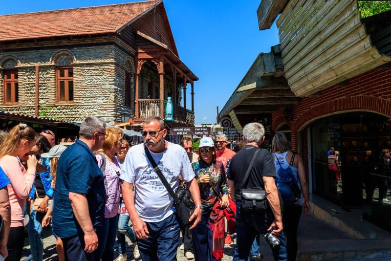 Touristen, die auf Straße mit Geschenksouvenirladen in der historischen Stadt von Mtskheta gehen stockbild