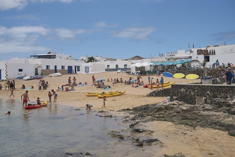 Touristen, die in Caleta Del Sebo ein Sonnenbad nehmen und schwimmen lizenzfreie stockbilder