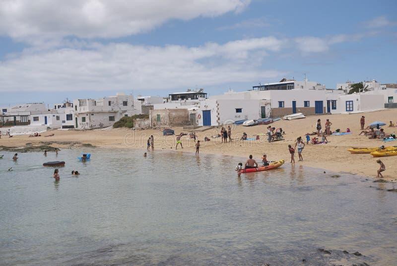 Touristen, die in Caleta Del Sebo ein Sonnenbad nehmen und schwimmen stockfoto