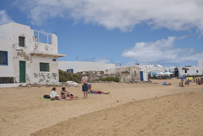 Touristen, die in Caleta Del Sebo ein Sonnenbad nehmen und schwimmen lizenzfreies stockfoto