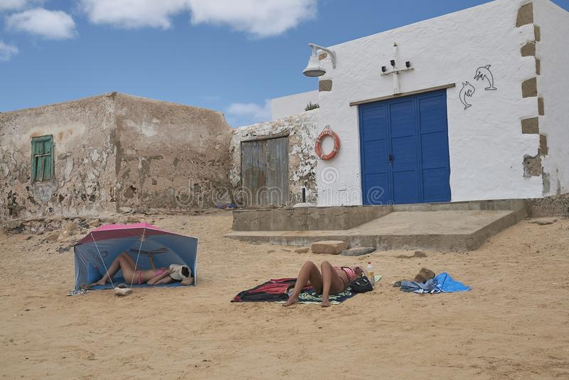 Touristen, die in Caleta Del Sebo ein Sonnenbad nehmen und schwimmen stockfotografie
