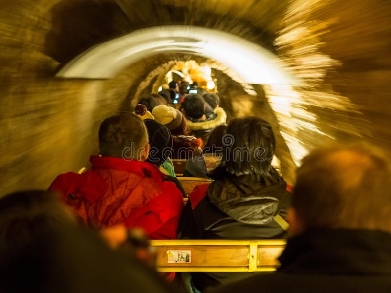 Touristen, die den Zug durch die Postojna-Höhle reiten lizenzfreie stockfotografie