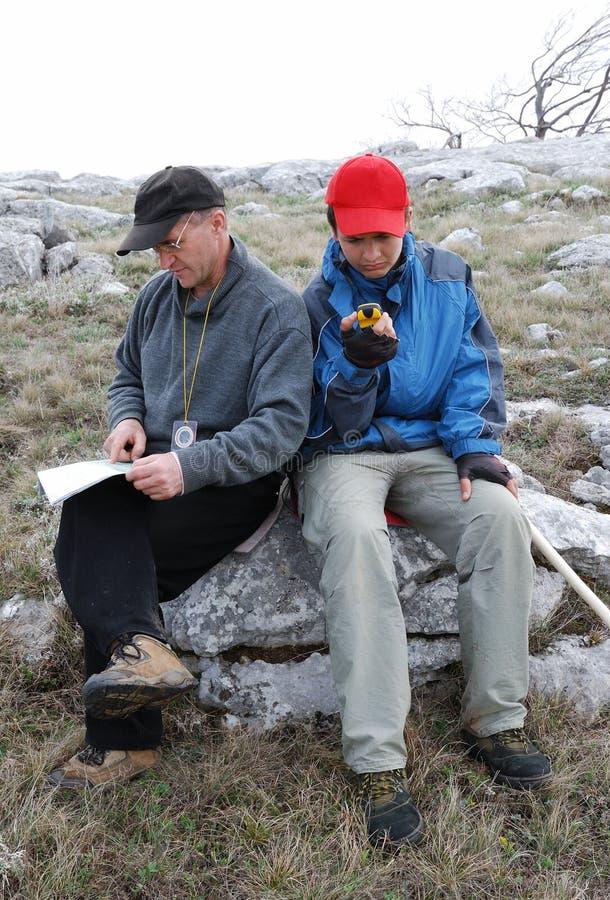 Touristen, die durch Karte und GPS orienteering sind. stockbilder