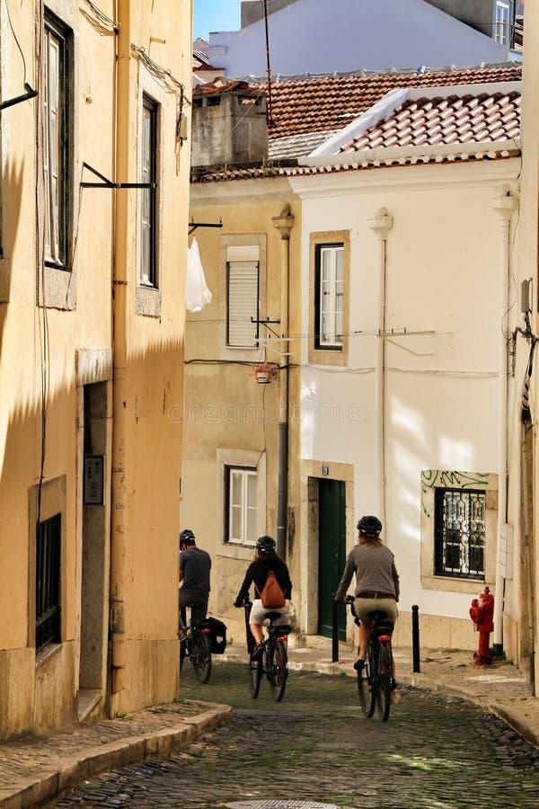 Touristen, die durch die Straßen von Lissabon radfahren stockbild