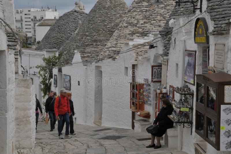 Touristen, die entlang eine schmale Straße in Alberobello, Apulien-Region, Süd-Itay gehen lizenzfreies stockbild