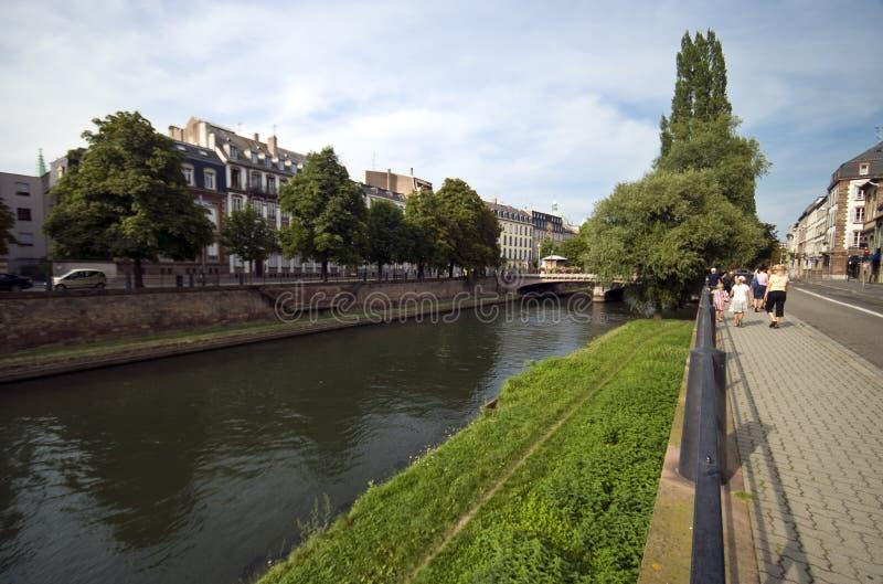 Touristen, die entlang einen Fluss in Straßburg gehen stockfoto