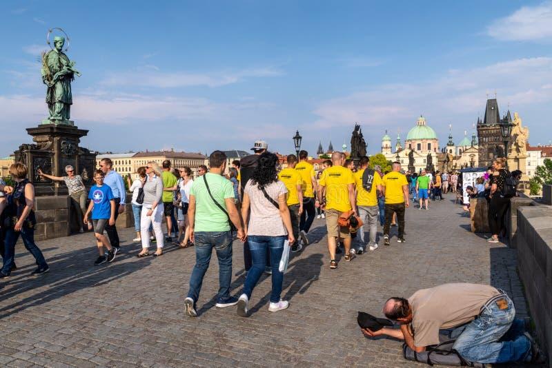Touristen, die für Bilder beim Ignorieren eines begger in der Gebührenbrücke, Prag gehen u. aufwerfen lizenzfreies stockbild