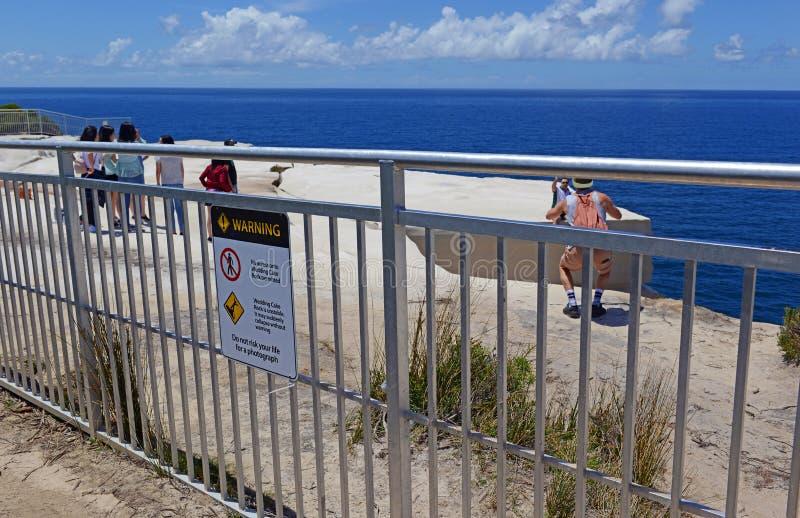 Touristen, die im riskanten Verhalten im königlichen Nationalpark, Sydney Australia sich engagieren lizenzfreies stockfoto