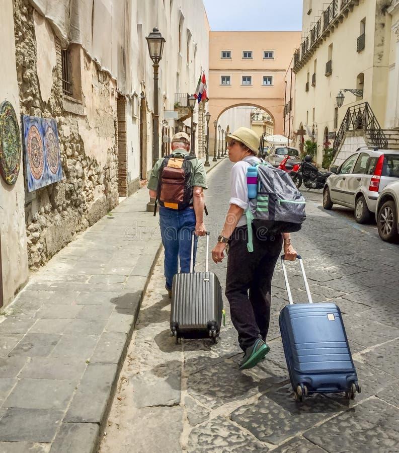 Touristen, die Koffer hinunter Straße ziehen lizenzfreies stockbild